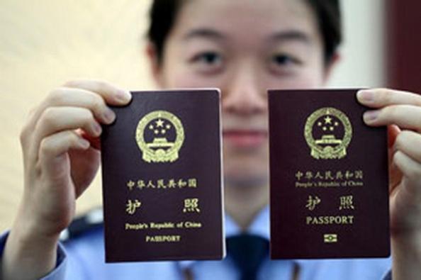 AFPMột nữ công an Trung Quốc ở Giang Tô so sánh hộ chiếu Trung Quốc cũ (bên trái) và hộ chiếu điện tử mới (bên phải) hôm 14-5-2012.
