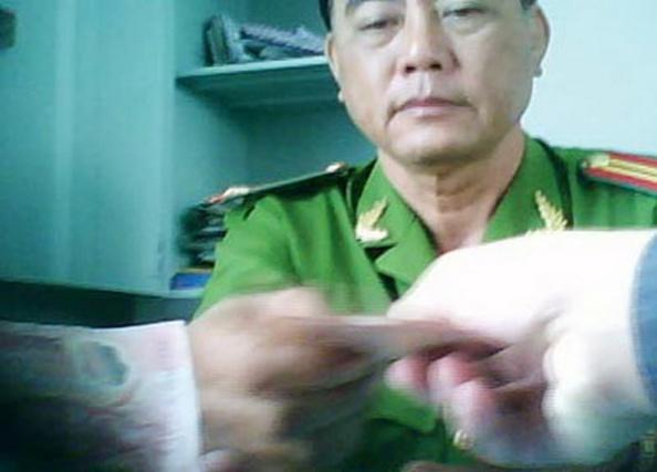 Trung Tá Thiều Quang Văn nhận tiền bảo kê xe của anh H. (Hình: Thanh Niên)