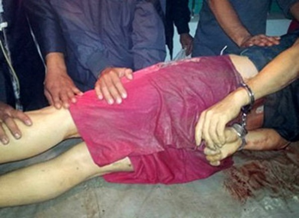Nạn nhân Bùi Văn Lợi sau khi trúng đạn của công an, tử vong tại bệnh viện, vẫn trong tình trạng bị còng tay ngày 14 tháng 12, 2012. (Hình: Tiền Phong)