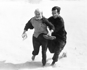 A Roman Catholic priest aids an elderly villager to brave the windy rotor blast from a government helicopter as they run to board it from west of Tuy Hoa in Vietnam, Wednesday, March 27, 1975. They were among thousands of refugees from the Central Highlands who were picked up along the central coast.