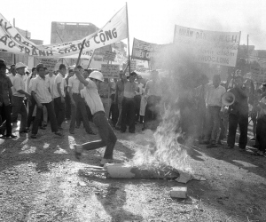 Anticommunist demonstrator kicks burning effigy of Viet Cong soldier during unruly protest outside Saigon headquarters of International Commission of Control and Supervision in Saigon, Jan. 6, 1975. About a hundred demonstrators protested fierce fighting in Phuoc Long province in violation of the Paris peace agreement, which the ICCS is charged with enforcing.