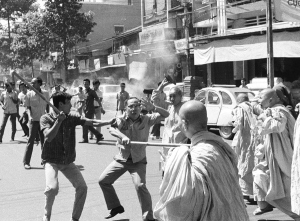 Two stick-wielding plainclothes policemen fight South Vietnamese Buddhist nuns in Saigon, Sunday, Jan. 26, 1975 during anti government demonstration. Officer (left) warns comrade that nun (background) is about to hit him with sandal. Melee occurred following political convention at pagoda.