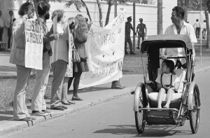 A little girl in a pedicab, and her driver stare as they pass a demonstration of nine anti-war activists before the United States embassy in Saigon, Friday, Jan. 25, 1975. The activists, led by David Harris, left, of Menlo Park, Calif. former husband of folk singer Joan Baez, passed out leaflets demanding the end of U.S. intervention in South Vietnam.