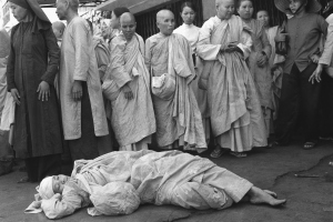 South Vietnamese Buddhist nun injured in melee between police and about 20 nuns staging demonstration rests on floor at pagoda surrounded by other activist religious in Saigon, Sunday, Jan. 26, 1975. Antigovernment protest and fighting followed political convention. Four nuns were injured, none of them seriously.