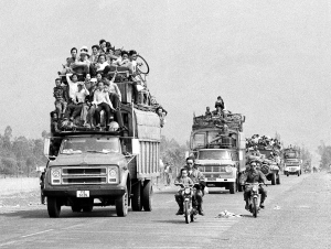 Trucks and motorbikes, loaded with refugees, roar along the main highway from the old imperial capital of Hue to the port city of Danang about 50 miles south of Hue, March 25, 1975. Hue's 200,000 inhabitants have been streaming southward since the Saigon government?s decision to abandon the city in the face of a heavy North Vietnamese buildup.