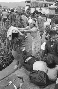 Injured victims of a road accident in the panicky flight from Hue stand over a dead woman in Hai Van Pass, March 21, 1975. Fatal accidents and injuries were common among the thousands of refugees who fled advancing North Vietnamese, and attempted to find refuge in the coastal city of Da Nang.