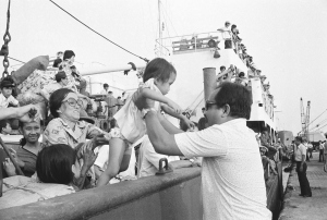 Father and mother, from front and back, help lift their youngster from ship to dock as the family and hundreds of other refugees arrive at Saigon dock, Friday, March 29, 1975. The arrival of the merchant vessel was one of the first at the capital since the mass exodus of South Vietnamese from the central highlands and Northern provinces. (AP Photo/Phuoc)