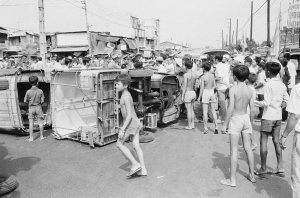Saigon youngsters mill around overturned three wheeled minibuses during a demonstration by the vehicle's drivers protesting various economic issues. The protest was one of two which tock place, March 25, 1975 in the South Vietnamese capital Saigon.
