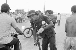 A crippled South Vietnamese war veteran limps away on crutch with food looted from abandoned U.S. installations after evacuation of Saigon, April 29, 1975. (AP Photo)