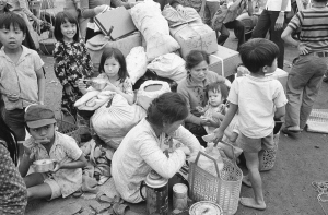Their household goods in a haphazard pile, a South Vietnamese refugee family takes time out for lunch at Da Nang in Vietnam, March 28, 1975, where they are waiting to be relocated after fleeing from the Northern provinces. (AP Photo/Phuoc)