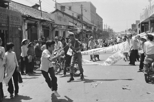 A Saigon student demonstrator hastily flees after a policeman grabbed his antigovernment banner, Thursday, April 9, 1975. About 30 students protested the draft and demanded the ouster of South Vietnamese President Nguyen Van Thieu. (AP Photo/Dang Van Phuoc )