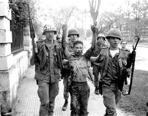 Photo by Bill Snead-The last Vietnamese taken out of the United States Embassy during the Tet Offensive of 1968, the offensive that changed the war. The prisoner, holding a U.S. identification card in his hand, was taken to the back of a nearby hospital and shot by Vietnamese military police.  Photo 8. Last VC in US Embassy- US Military Policemen escort the last probable Viet Cong found inside the U.S. Embassy during the Tet Offensive fighting in Saigon, February, 1968. Most of the American and South Vietnamese troops were positioned outside the city leaving the MP's to battle Viet Cong who had infiltrated the city.  The prisoner, holding his U.S. government identification card, was taken to a nearby hospital, escorted to the back of the building and shot by South Vietnamese military policemen