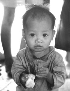 Photo 7. -Casualty of war --Vietnamese baby whose parents were killed during fighting near Bien Hoa eats grapefruit in a refugee camp, oblivious of her situation.  After this photo was transmitted across the world by United Press International hundreds of offers to adopt the child were received by the news service. Returning to the refugee camp we found the child gone with no records of where she went. A hunt for the child was unsuccessful.