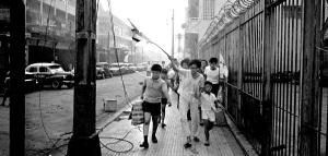 Civilian residents of a Saigon suburb scurry out of their neighborhood, some waving white flags,  to a quieter part of town during fighting. In some cases the Viet Cong would infiltrate an area individually and regroup before dawn attacking strategic targets.