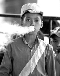 Vietnamese Jockey: A young jockey gets creative with the smoke from his Salem cigarette between races at the Phu To Race Track on the outskirts of Saigon. Racing continued in Vietnam until the1968 Tet offensive when the racetrack became a command post filled with American tanks artillery and armored personnel carriers.